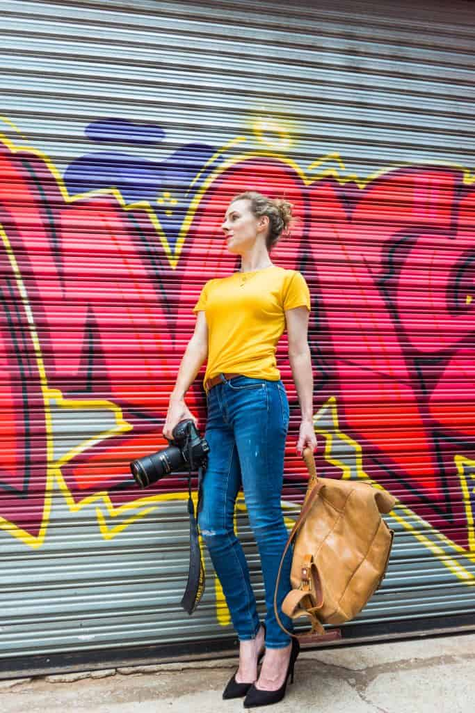 Photographer in front of graffiti wall with camera and bag - personal branding photography.