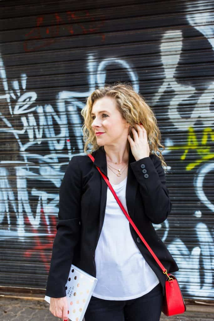 Woman in front of graffiti with red bag - personal branding photography.