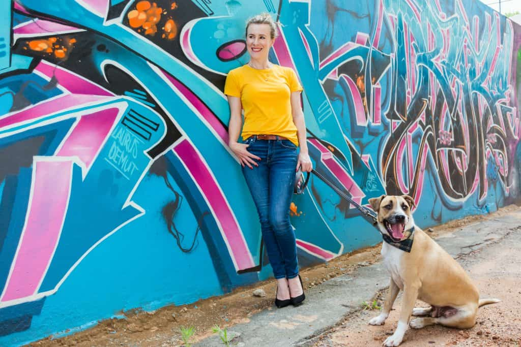 Woman with dog in front of blue graffiti wall.