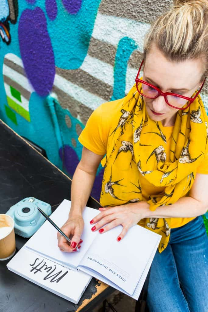 Woman with yellow scarf writing in a book - personal branding photography.