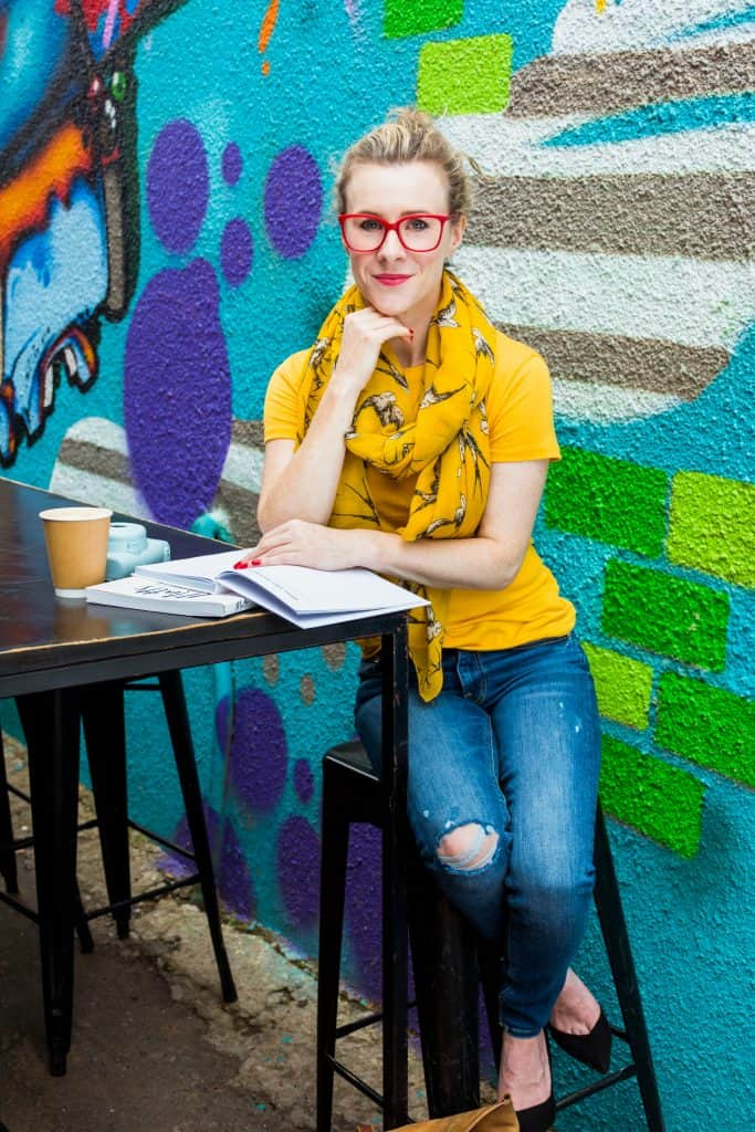 Woman sitting at a table with a book - personal branding photography.