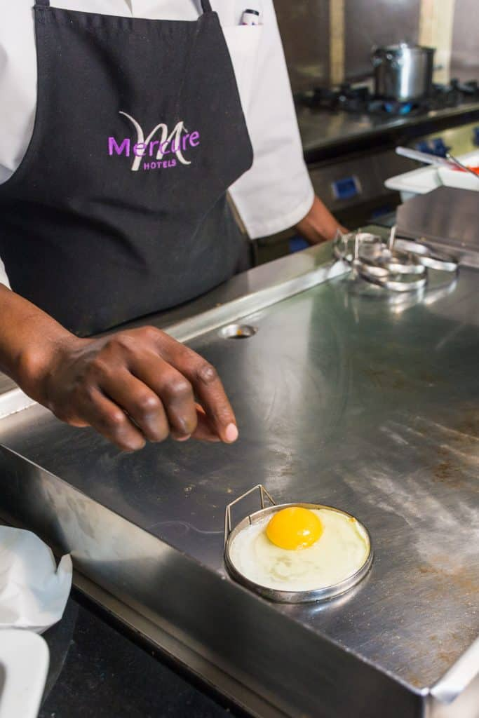 Hotel lifestyle photography staff frying egg for breakfast guest