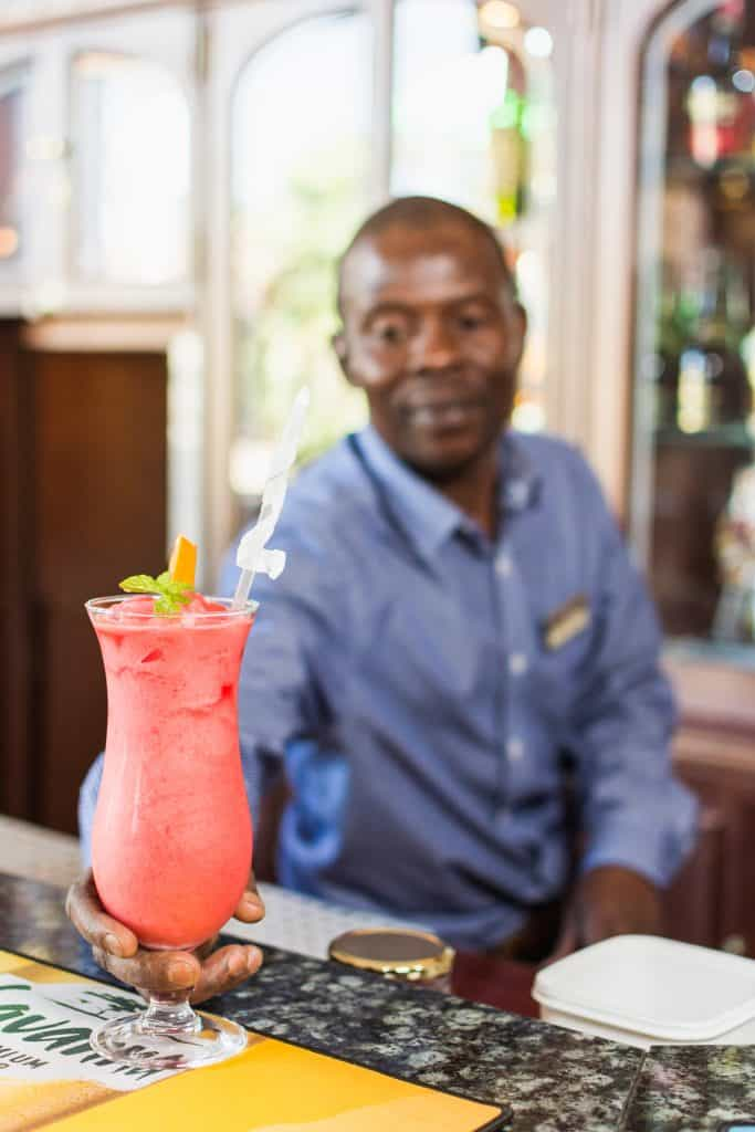 Hotel barman serving red cocktail