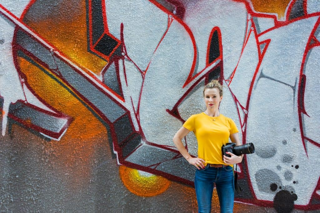Photographer posing in front of graffiti wall - branding photography.
