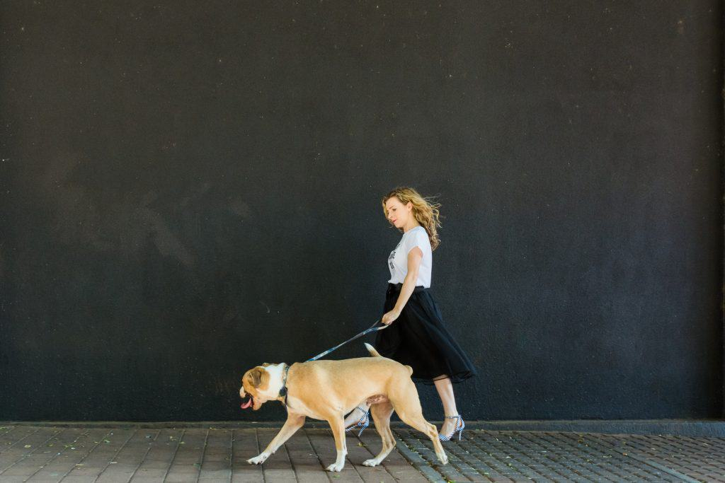Woman walking with dog in front of black wall - branding photography.