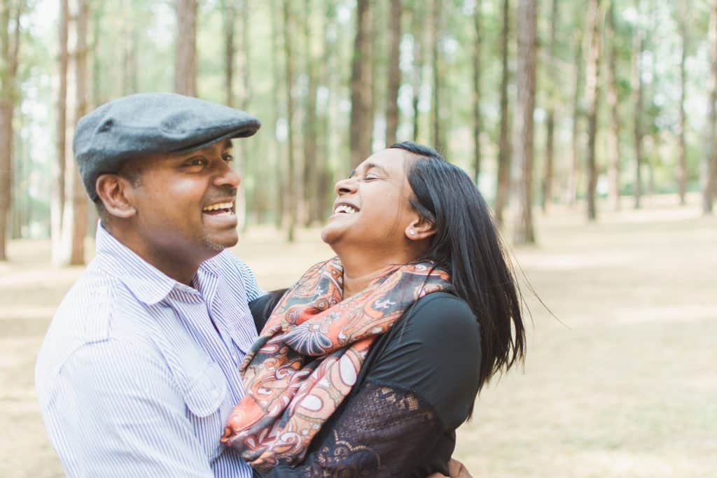 Couple laughing in a pine forest - lifestyle photography.