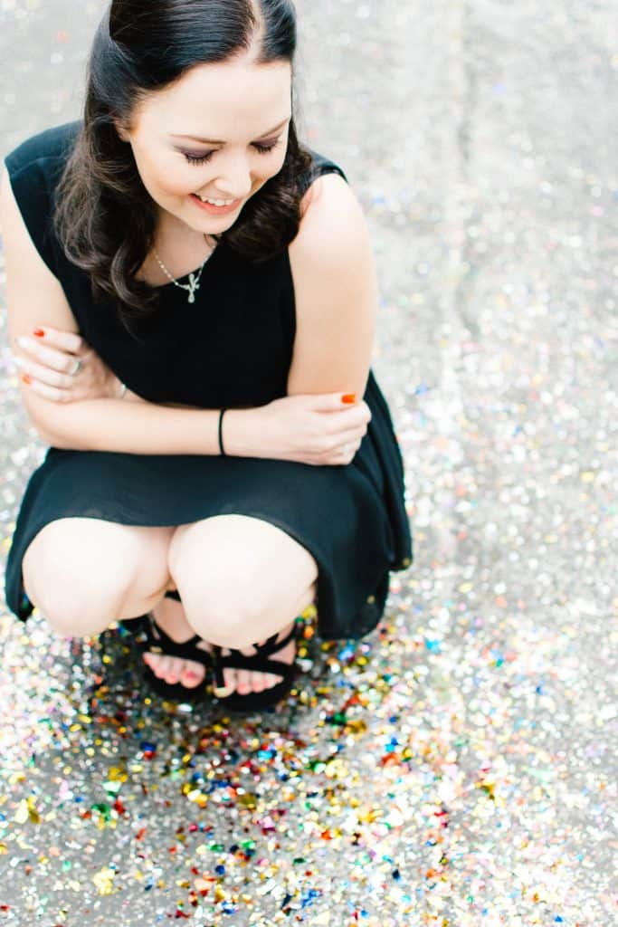 Woman smiling with foil confetti - lifestyle photography.