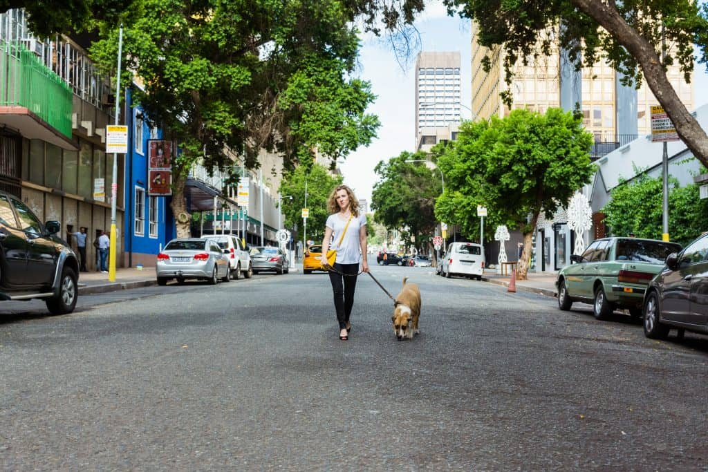 Woman walking on city street with dog.