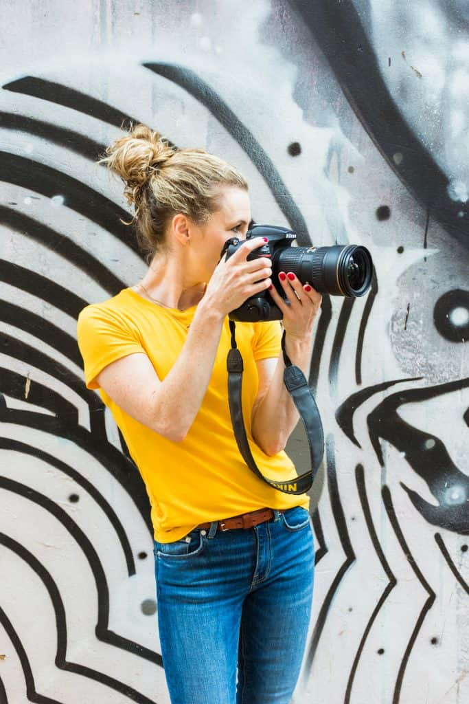 Photographer with camera in front of zebra graffiti - personal branding photography.