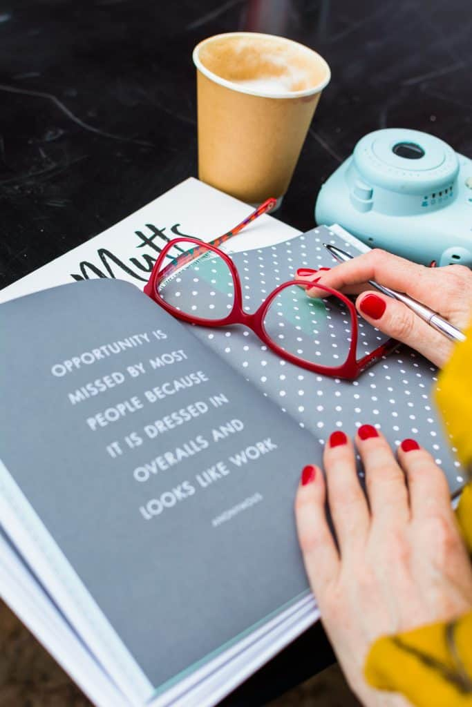 Woman's hands on book with red glasses - personal branding photography.