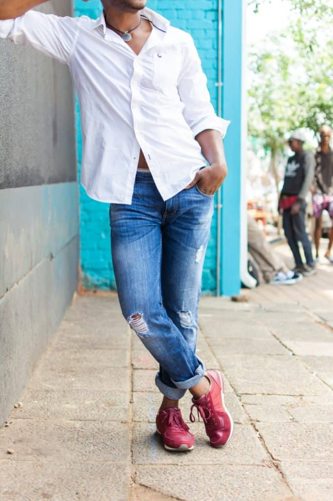 Man's legs wearing jeans and red shoes
