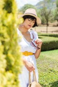 Lady in white dress with a hat and sunglasses